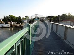 A bridge over the water allowing the pedestrian walkway and the roadway to lift and let the sailboats through.