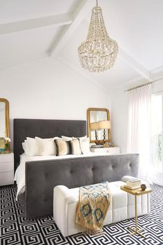 Glam bedroom boasts a vaulted ceiling adorned with a Oly Studio Flower Drop Chandelier illuminating a dark gray tufted bed with footboard dressed in soft white bedding flanked by gold beaded mirrors leaning against two white 3 drawer nightstands.