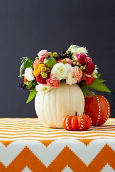 There's a secret to this squash centerpiece. Hollow out the gourd, then hide a water-filled vase inside for long-lasting blooms. Stud mini pumpkins with brass tacks for an extra pop. Click through for the tutorial and more DIY Halloween decorations.