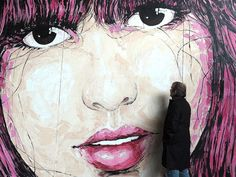A visitor looks at a mural by street artist El Bocho at the Urban Art Graffiti 21 exhibition at the Volklingen Ironworks on March 21 in Saarland, Germany