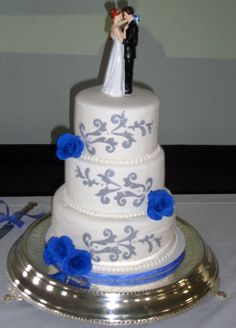 Cobalt blue roses and silver filigree on white cake.