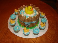 "8"" 2-layer round cake surrounded by pirouettes with a rubber duck on top. Cupcakes surround with chocolate ducks for decor"