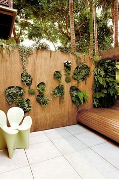 Make the most of small spaces with vertical green walls. Here, shade-loving succulents and ferns perch prettily in petal...
