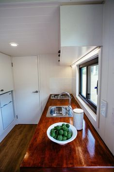 The kitchen includes a cooktop, sink, and small refrigerator. A large pantry is located across from the kitchen counter.