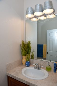 Beach Bathroom. Bucket lights. Like the vases how they match the towels