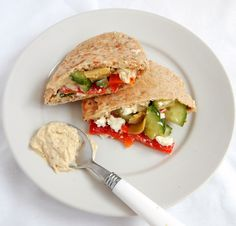 Vegetarian Sandwich with hummus, roasted red peppers, artichoke hearts, feta cheese, and cucumbers.