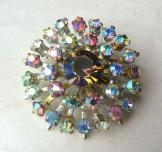 A stunning vintage aurora borealis atomic style rhinestone brooch.  Studded with a large central rhinestone which is surrounded by two circles of smaller rhinestones in a layered design.  The rhinestones are set against a silver tone metal.  Vintage circa 1960's