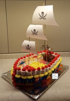 Mon gâteau de bonbons bateau de pirate! Une très bonne idée qui a été appréciée aussi bien par les enfants que par les parents. La base une coque de barque en polystyrène recouvert d'aluminium. Les bonbons pour recouvrir la coque ont été piqués avec des cure-dents et les autres juste posés plus pratique pour les jeunes enfants.