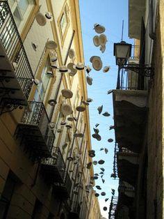 Hats hanging between buildings in Palermo- Sicily