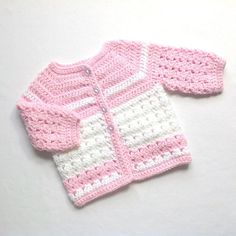 Age 0 to 3 months. This is a crochet baby set with a little coat, PomPom hat and booties in a medium weight, acrylic yarn in pink and white. The bobble hat has a turned up brim and the little boots have a matching turn-down. Measurements are below. To fit chest ..... up to 19 (48 cms)