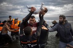 Wedesday, Nov. 25: The Turkish Coast  -  A volunteer holds up a baby as others help migrants and refugees to disembark from a dinghy after their arrival from the Turkish coast to the Greek island of Lesbos on Wednesday, Nov. 25, 2015. About 5,000 migrants reach Europe each day over the so-called Balkan migrant route.  -    © Santi Palacios/AP