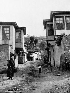Κρατώντας ένα μπολ με φαγητό στο χέρι, κατεβαίνει το μισοστρωμένο καλντερίμι. Αρχές της δεκαετίας του 1910.