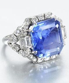 A sapphire and diamond ring, circa 1935. The cut-cornered step-cut sapphire in a finely pierced scrolling foliate mount set with single and baguette-cut diamonds, millegrain detail throughout, diamonds approx. 0.90ct total.