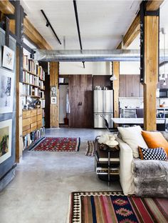 Wooden columns, revealing piping and duct work, cement flooring...modern details with industrial features!! So sick!!