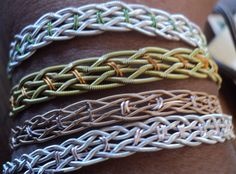 This is one of the first things I made with guitar string. It looks a lot more complicated than it is, it is just two three strand braids, side by side, sewn together with wire.
