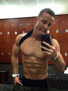 Jorge Guevara lifts his tanktop and does a mirror selfie to show off his 6pack and pecs