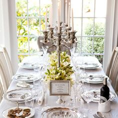 """Break out the good stuff for a class-act formal dinner party. Inspired by PBS's """"Downton Abbey,"""" the room is transformed into the picture of old-world aristocracy. Exquisite china, intricate cut crystal, and ornate flatware atop pressed linens surround stately candelabras and flower-filled silver bowls. A pedestal photo frame displays the evening's menu."""