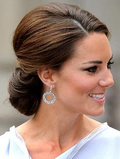KATE MIDDLETON, The Duchess gives her slim gray Roksanda Ilincic sheath a twist by pulling her long chestnut locks into a romantic, sculpted chignon with volume at the crown.