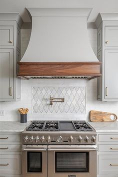 Light gray French hood with an oak trim in a transitional kitchen cooktop above a Thermador range flanked by marble countertops. Kitchen Hood Design, Kitchen Vent Hood, Country Kitchen Designs, Kitchen Redo, Home Decor Kitchen, New Kitchen, Home Kitchens, Kitchen Remodel, Kitchen Country