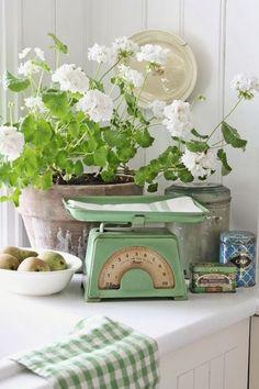 Brocante hoekje in huis in groentinten met vintage weegschaal en tinnen blikken