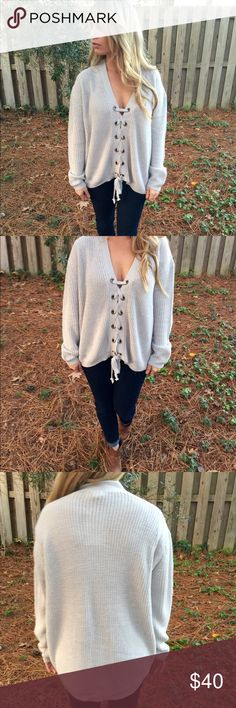 Lace up sweater This sweater features an adjustable lace up front and long sleeves. Pair this top with jeans jeans and boots in the winter and white pants and sandals in the spring.  -Wearing size small  - 55% cotton  -45% Acrylic Sweaters V-Necks