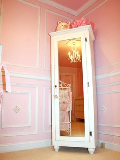 This thin armoire is the perfect size for a girl's nursery. The white wood matches the wall paneling. The mirror reflects the traditional chandelier hanging above the white iron crib.