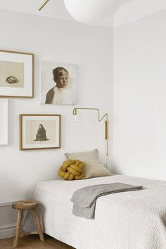 modern bedroom with art on wall behind bed and gold wall light fixture. / sfgirlbybay