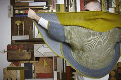 I was knitting a striped shawl and felt lost as I didn't know what to knit next. I found my way by deciding to turn the shawl into a jacket! This garment begins with a semi-circular top down shawl decorated with stripes and short rows. The ribbed back and garter stitch sides grow from picked up stitches. Two front seams mold the fabric into a convertible garment. Wear the garment upside down for even more drama.