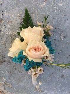Boutonnière of blush spray rose with teal caspia, white wax flower, and a touch of fern