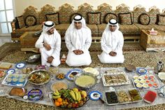 Ras Al Khaimah -  Brothers, left to right, Ali, Saeed and Abdullah Al Qaishi with sweets and other foods to celebrate Eid with family and friends in the home near Rams.  Jeff Topping / The National