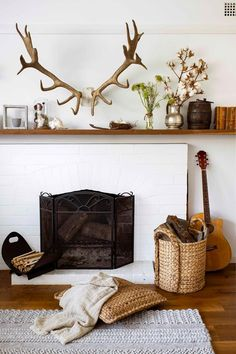 white brick fireplace with vintage treasures and antler husks Cosy Fireplace, Brick Fireplace, Fireplace Ideas, Brick Look Tile, Timber Gates, Cosy Night In, Furniture Village, Kitchen Benches, Australian Homes