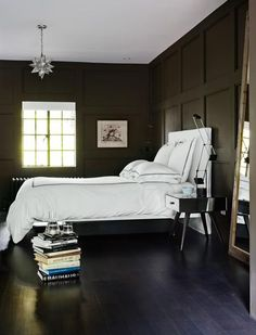 bedroom | Deep charcoal-grey paint, paneled walls, crisp white hotel-style bedding, star light fixture, mirrored night table