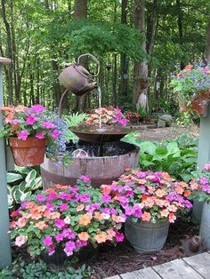A marvelous Garden Fountain constructed of recycled things! It is surrounded by gorgeous potted flowers.