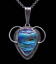 This is not contemporary - image from a gallery of vintage and/or antique objects. MARGARET WILSON  A Glasgow, Arts & Crafts, silver pendant set with abalone suggesting a rugged island seascape.