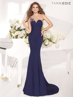 Show them how chic you can be in this tantalizing Tarik Ediz 92092 evening dress. So sleek, this asymmetrical sweetheart gown has a crystal motif at the shoulder forming a single strap and a sheer overlay covering the decollete. It hugs the body as it falls floor length in a slight flare for a stunning fluted look.