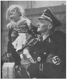 An Allgemeine SS officer holds his daughter during celebrations somewhere in prewar Germany, unknown date