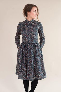 Collarless shirt style dress, handmade in a lovely navy floral Liberty of London tana lawn fabric. Fitted bodice with button opening down the chest and long sleeves with button fastening on the cuffs. Gathered skirt with in seam pockets and concealed zip fastening down the side. All