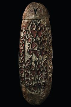 "Papua New Guinea, Asmat mangrove wood, brown patina, painted with red, white and black pigment, oval compartment in the centre decorated with flying fox figures in bas-relief, geometrical patterns running around the rim, the stylized face on top depicting a stingray ""puru"", pierced rim for attachment of decorating tufts of sago leaf strips, carved handle backside, slightly dam., missing parts at the rim (above all right hand side and on top), rep., abrasion of paint H: 50.4 inch"