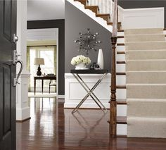 loving the berber on the stairs, white wainscoting, grey walls and rich wood floors!