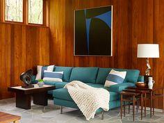 contemporary bohemian interior design mid century. Turquoise upholstered sofa, medium brown (teak?) paneling.