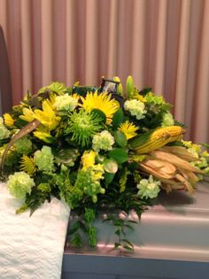 Funeral arrangement with John Deere Tractor and corn in it. Green  and yellow spider mums,green carnations and yellow mums.