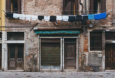 View of weathered building made of bricks. Clothes drying on rope. Daytime. Venice, Italy. Architecture gallery by Trent Lanz for Stocksy United - Royalty-Free Stock Photos. abandoned, background, brick, brickwall, building, cement, city, closed, clothes, concrete, day, daylight, dry, drying, entrance, europe, european, exterior, facade, hang, hang dry, hanging, horizontal, house, italian, italy, nobody, old, outdoors, plaster, rope, shabby, street, stucco, view, vintage, weathered, windows