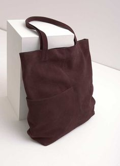 Stunning soft leather slouchy tote bag, perfect for work, shopping or to generally hold all of your essentials. In velvety bordeaux suede with a stylish outer pocket for added detailing. Bag measures 40cm/16in in height, width across middle is 40cm/16in, base width is 10cm/4in.