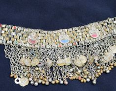 Vintage hand made Kuchi choker. Choker is lined. Made of base metal with colored glass. Metal color is a mix of golden and silver tones. Heavy weight. Old tattered fabric closures - you will need to add ties. Original lining needs to be sewn or replaced.  Fair to poor vintage condition - for parts and crafts use only. SEE PICTURES. Metal contains oxidation, discoloration and patina. Dangles are mismatched and bells are missing. Metal has been rapider in the past. This choker is very dirty…