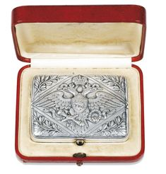 An Imperial Presentation Fabergé silver cigarette case, Moscow, 1908-1917, the lid cast and chased with an Imperial eagle within a lozenge, the corners with leaves and berries, the reverse engraved with signatures in Russian: Alexandra/ Olga/ Maria/ Tatiana/ Anastasia/ Alexei, cabochon sapphire thumbpiece, gilt interior. Provenance: presented to Nikolai Dmitrievich Semenoff-Tian-Shiansky, a commander aboard the Imperial yachts.