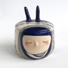 Lidded art vessel, deep blue carved lacework bunny with rosy cheeks.