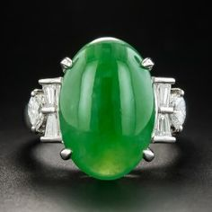 A big bold and beautiful natural Burmese jade cabochon, suffused with a richly saturated, translucent emerald green hue, glistens and glows between sparkling diamond bow motifs composed of marquise and baguette diamonds in this stunning and impressive estate jewel sturdily crafted in platinum. Accompanied by a gemological report from Stone Group Laboratory stating: Natural. No indications of polymers or dyes. Burma origin. 11/16 by 7/16 inch, currently ring size 6 1/4.