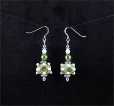 Nice earrings. Green and white lampwork glass bead earrings.   *Beads: Lampwork and glass beads   *Earwires: Sterling silver   *All other metal is silver plated.   *Length: 1.5 inches (from the bottom of the ear hook)   *Width: 0.75 inches (at the widest part)   *Handcrafted in Fayetteville, Arkansas