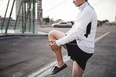 Athlete warming up and stretching before running photo by lenina11only on Envato Elements