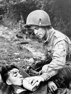 An American soldier gives a drink of water to a wounded German prisoner lying on a stretcher somewhere in the Normandy, on June 19, 1944, battle area through which the allies advanced. (AP Photo)